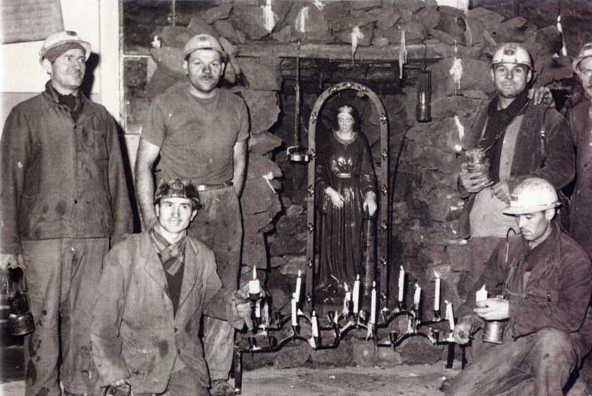 This picture shows a group of Italian miners with work overalls in the mine of Volmèrange-les-mines (France), next to Saint Barbara's statue (patron and protector of miners) during her celebrations. France, 1953.